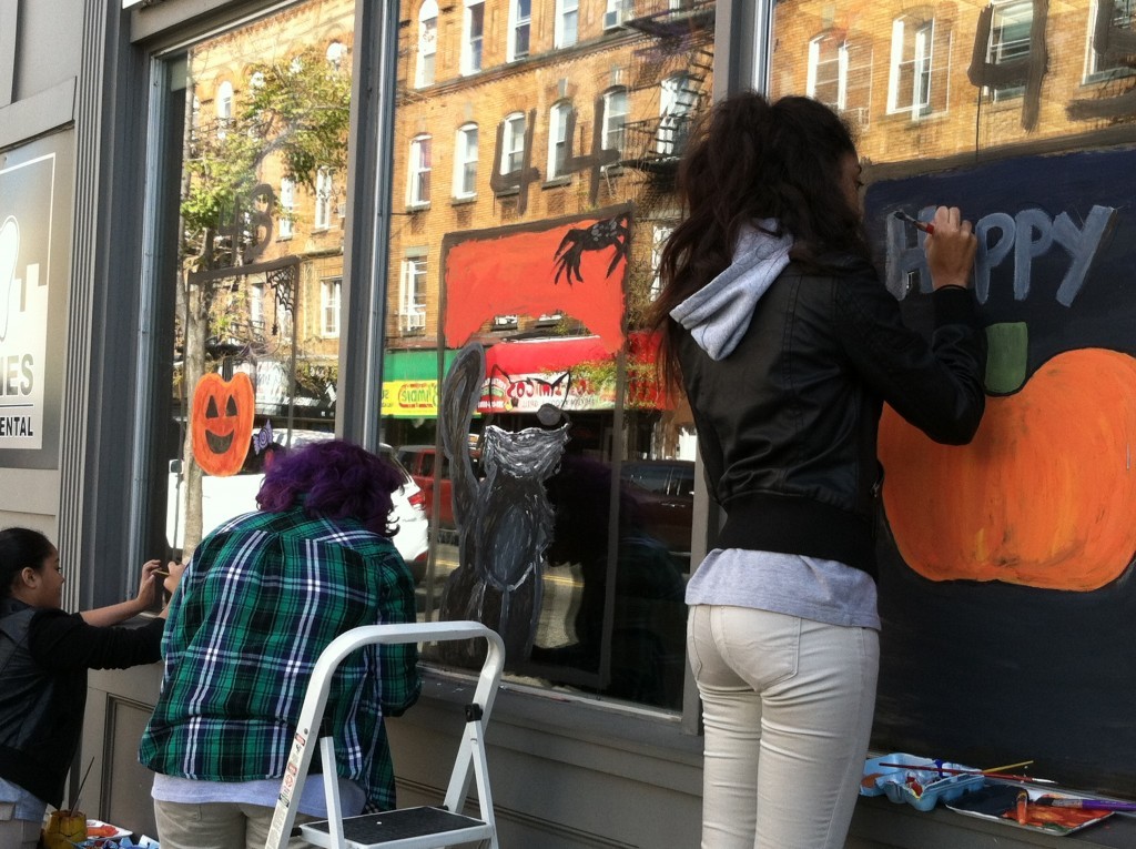 Students painting business windows for halloween in jersey city heights